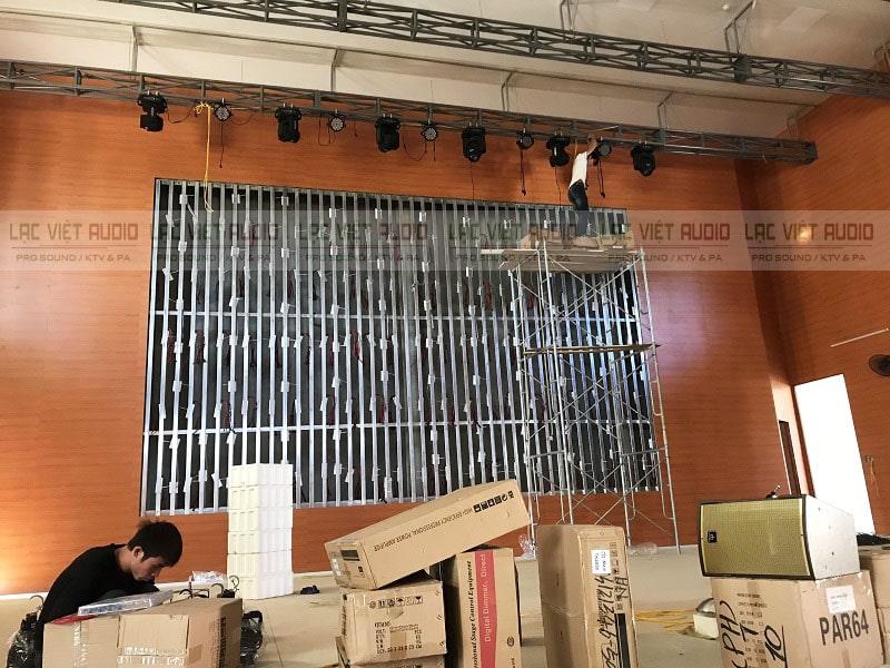 Nhân viên kỹ thuật Lạc Việt Audio đang treo đèn